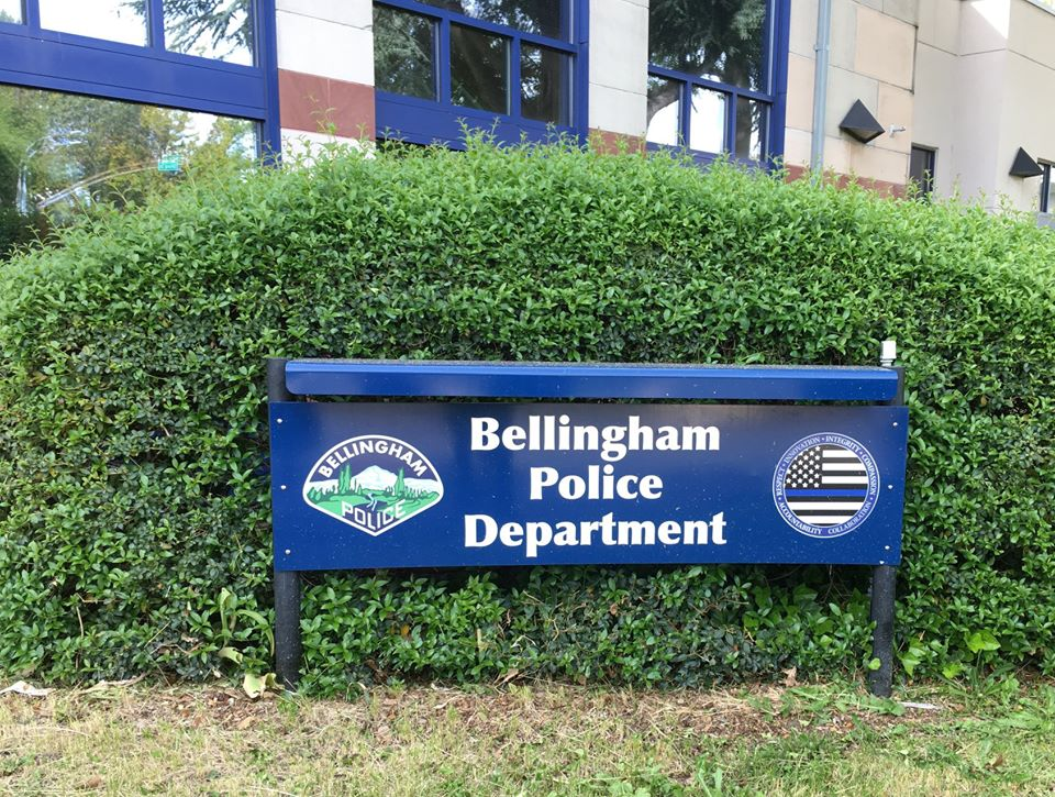 "A photograph of the sign outside the downtown Bellingham Police station that says ""Bellingham Police Department"". To the left of the words on the sign is the BPD crest and to the right is a circle insignia with a black and white American flag with a blue stripe just below the field of stars."